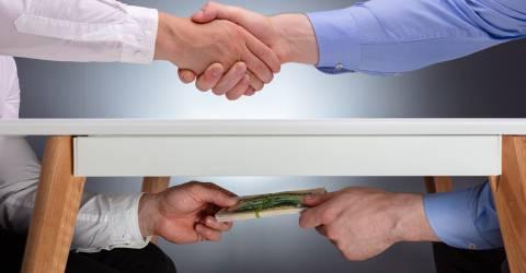 Handen schudden boven tafel en geld geven onder tafel. Fraude
